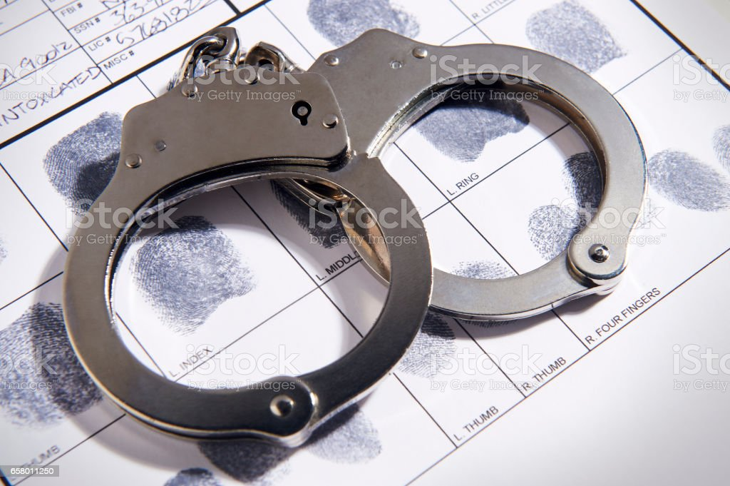Handcuffs laying on top of fingerprint chart in file stock photo