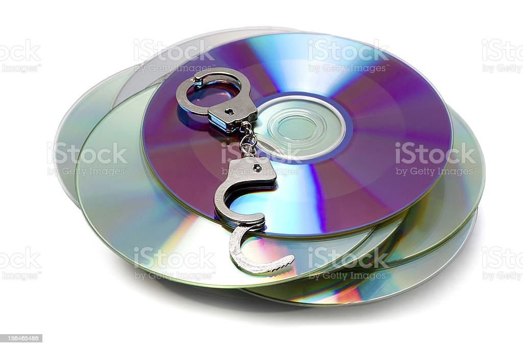 handcuffs on Compact Discs royalty-free stock photo