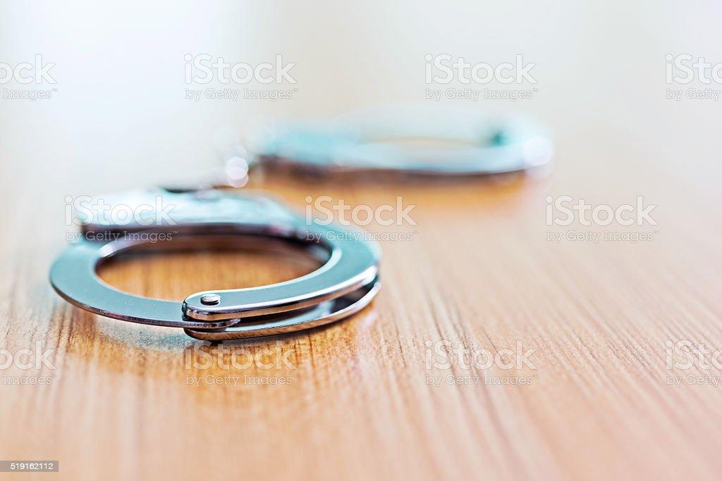 Handcuffs on desk stock photo