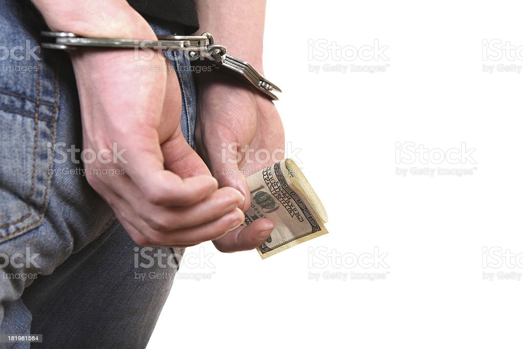 Handcuffs on Hands with Money closeup royalty-free stock photo