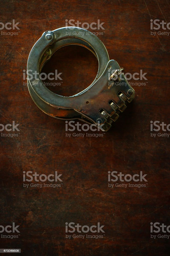 Handcuffs on old wooden table stock photo