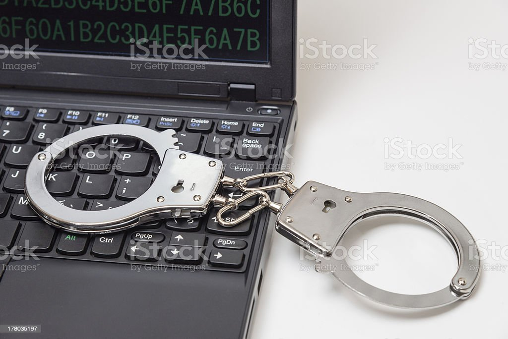 Handcuffs on the keyboard (XXXLarge) royalty-free stock photo