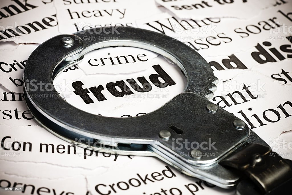 Handcuffs frame the word 'fraud' among newspaper cuttings stock photo