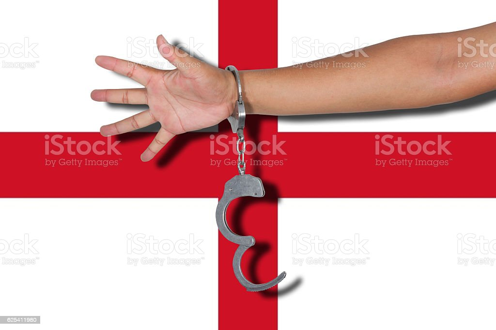 handcuffs with hand on England flag stock photo
