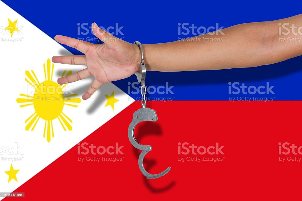 handcuffs with hand on Philippines flag stock photo