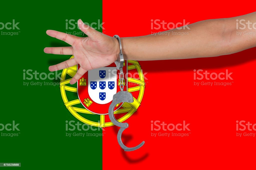 handcuffs with hand on Portugal flag stock photo