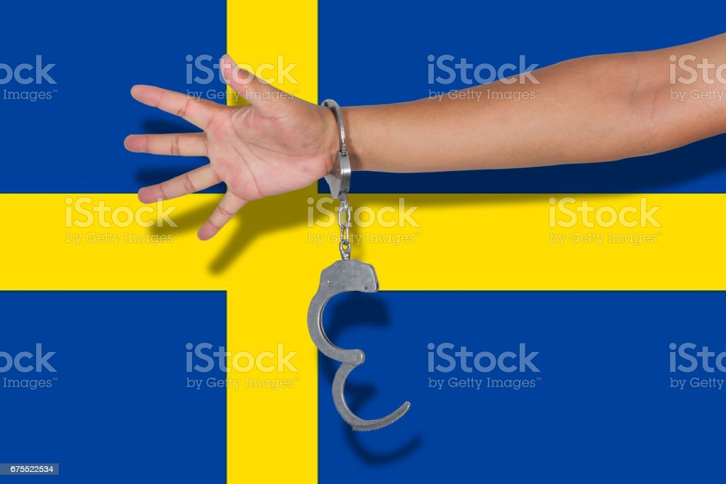 handcuffs with hand on Sweden flag stock photo