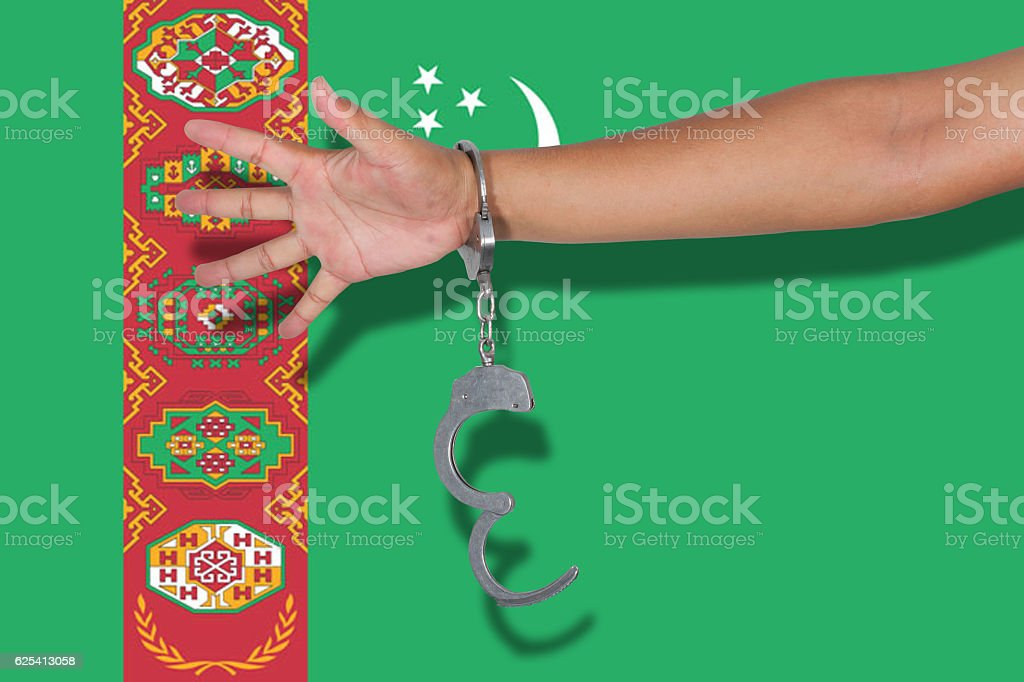 handcuffs with hand on Turkmenistan flag stock photo