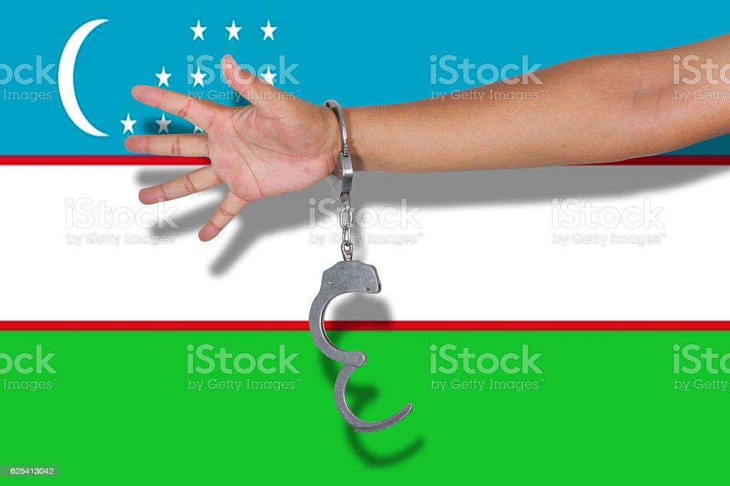 handcuffs with hand on Uzbekistan flag stock photo