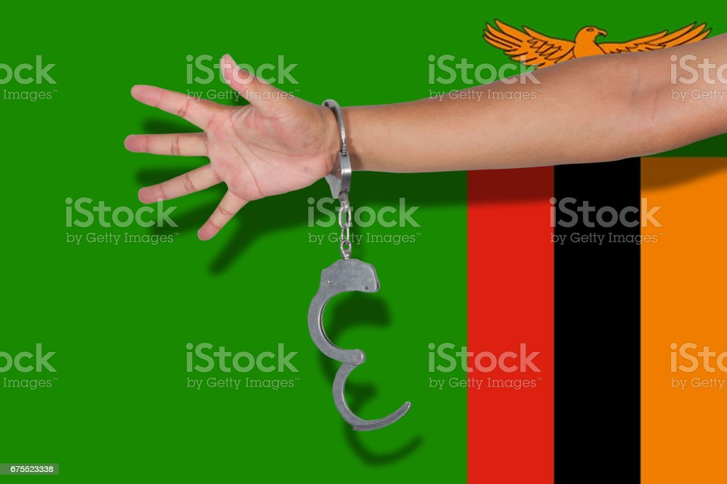 handcuffs with hand on Zambia flag stock photo