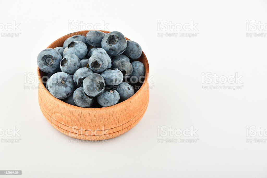 Handful of blueberries in wooden bowl isolated on white royalty-free stock photo