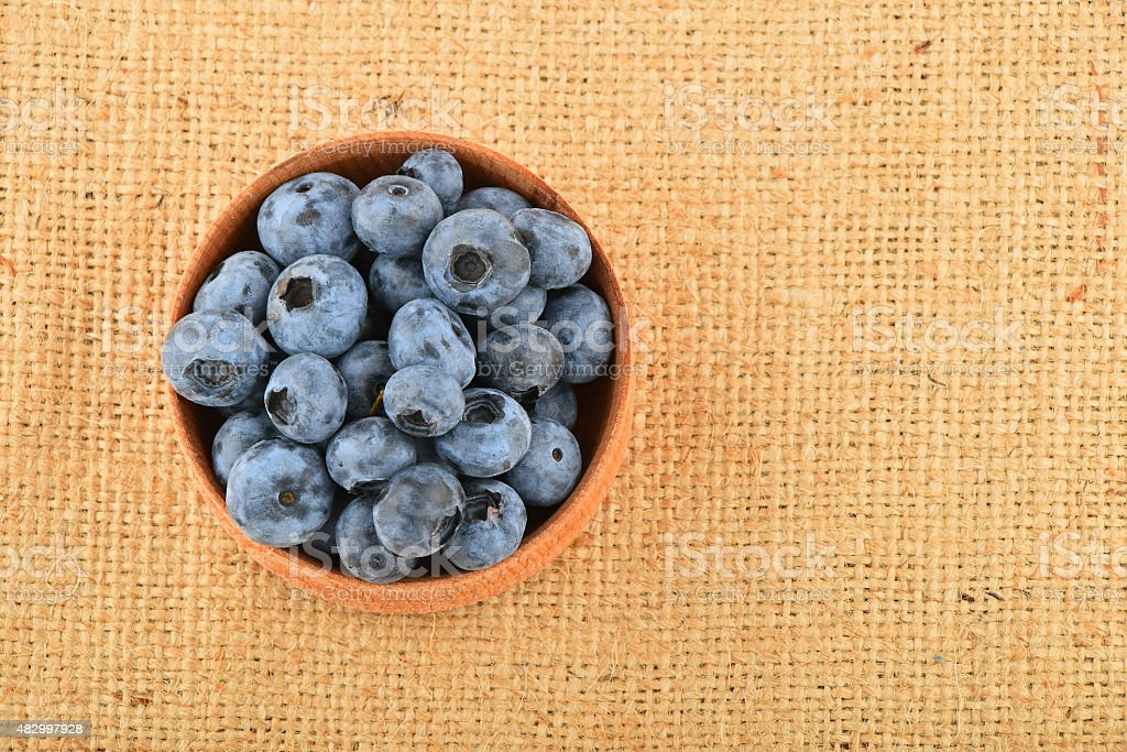 Handful of blueberries in wooden bowl on canvas royalty-free stock photo