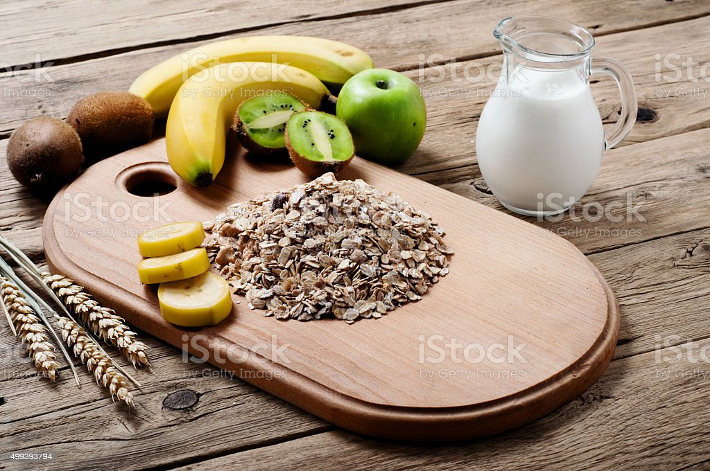 Handful of oatmeal with kiwi, apples, bananas and milk stock photo