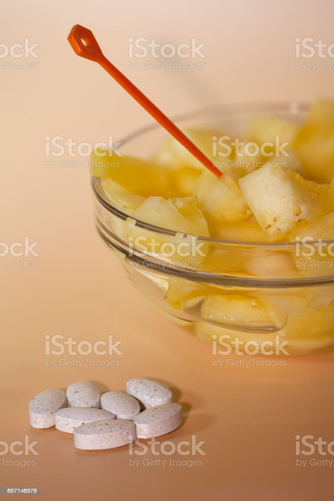 handful of pills and cup filled with pineapple slices stock photo