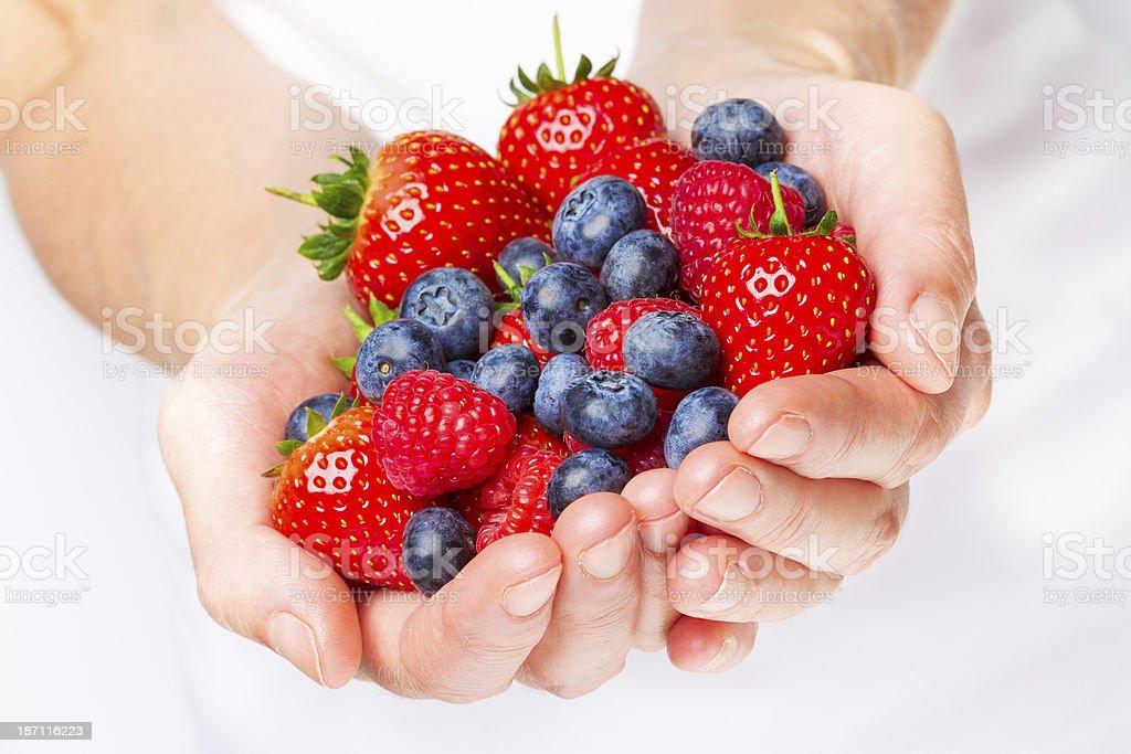 Handful of strawberries blueberries and raspberries stock photo