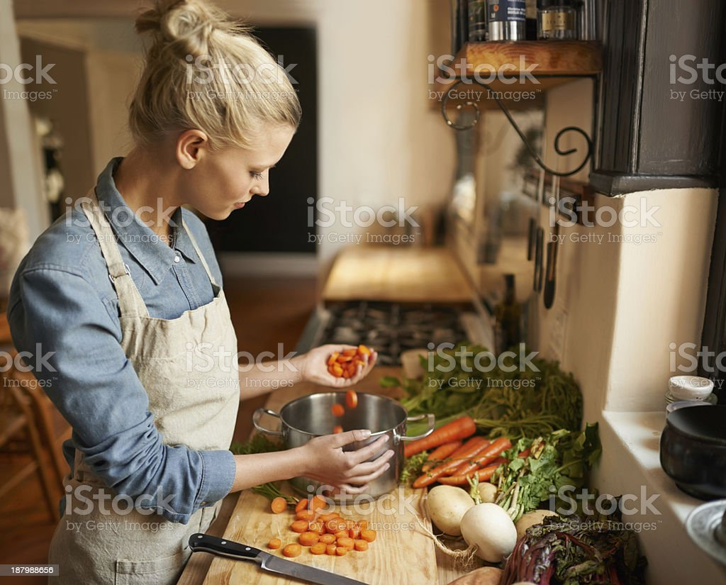 Cropped shot of a woman cutting carrots on a cutting board