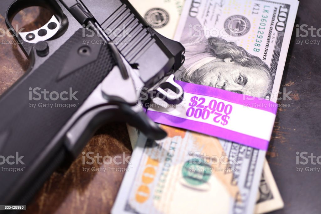 9MM handgun and stacks of $100 bills in $2000 wrappers. stock photo
