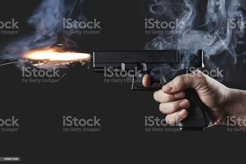 Handgun firing with fire and smoke stock photo
