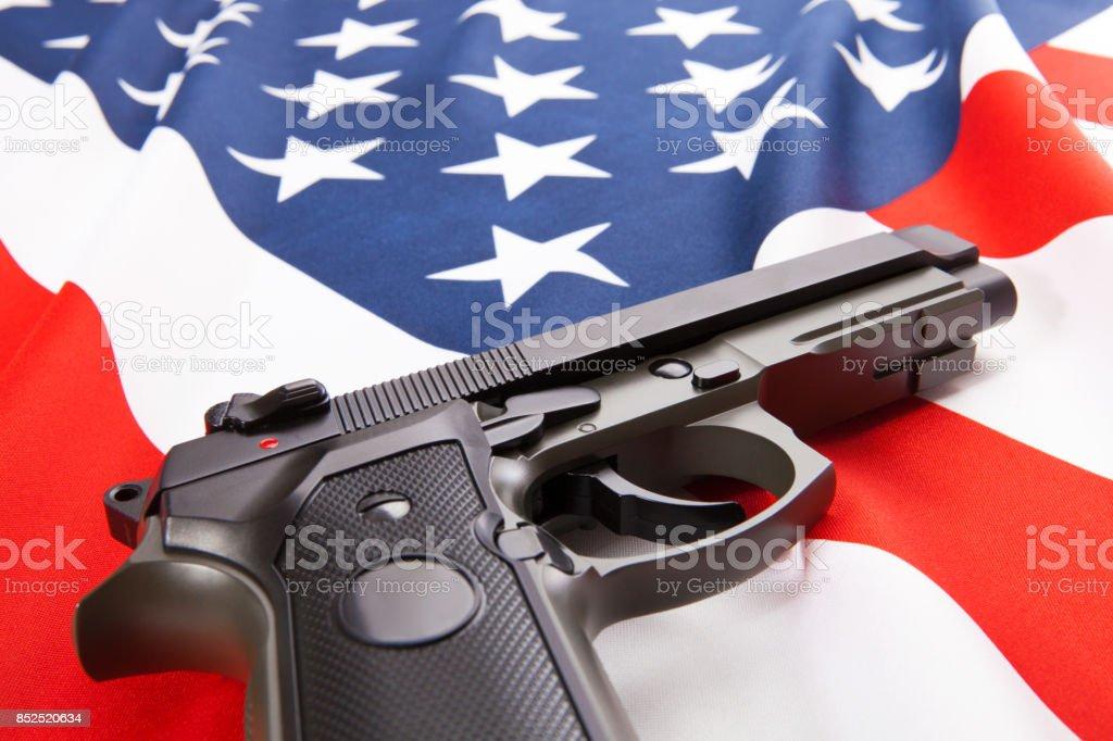 Handgun lying on satin US flag - close up studio shoot stock photo