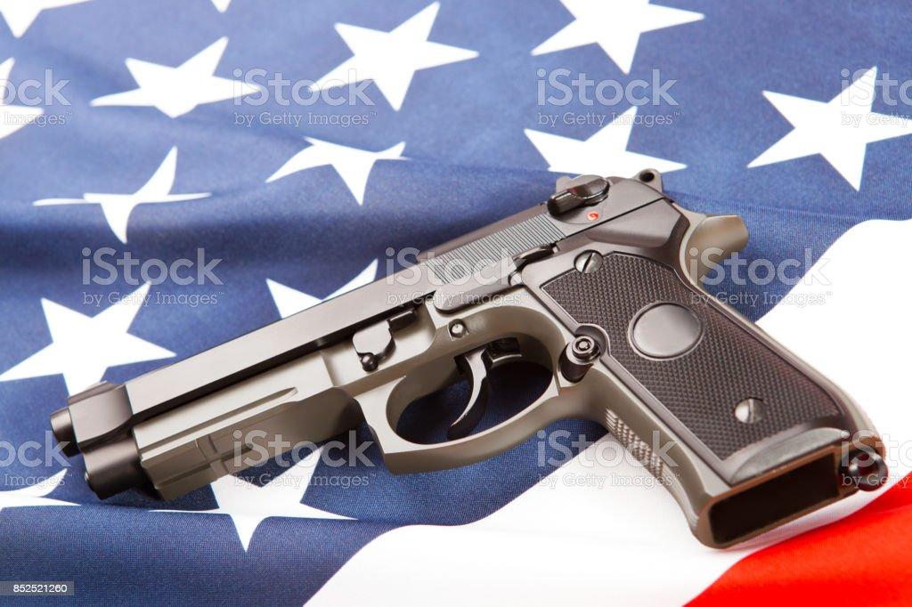 Handgun lying on satin US flag - studio shoot stock photo