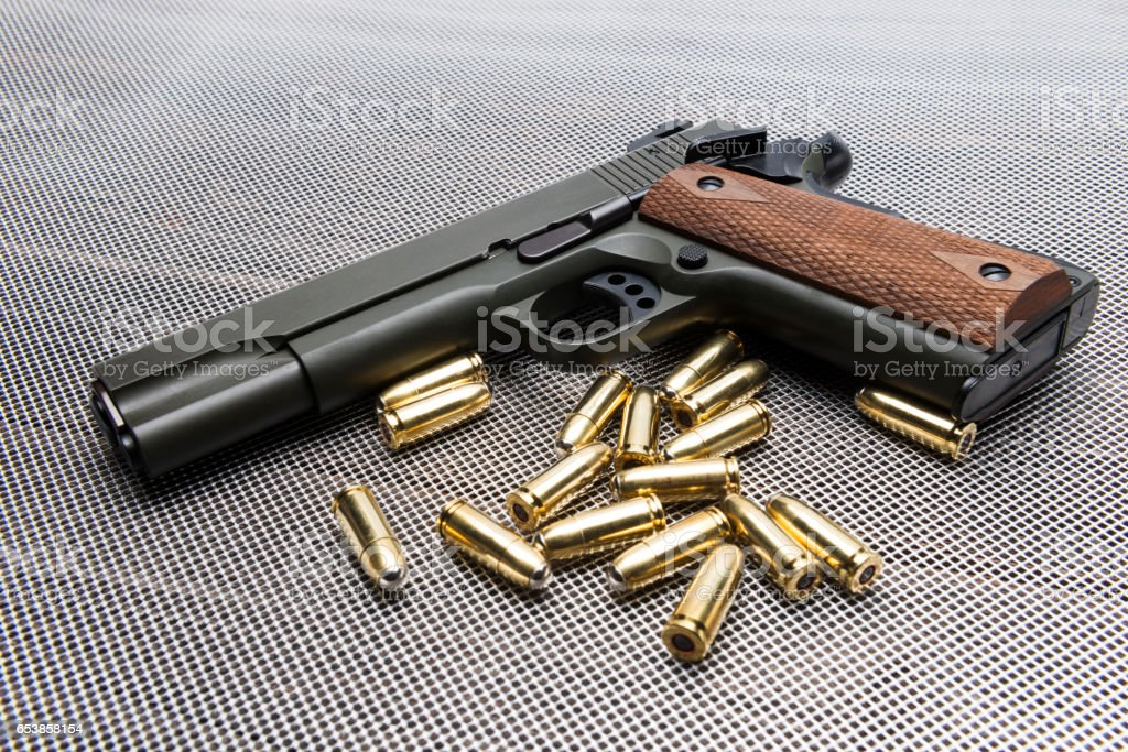 Handgun on metal net background stock photo