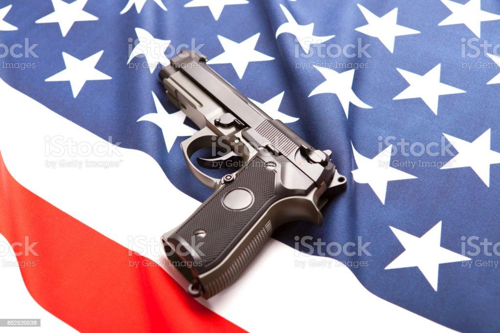 Handgun on satin US flag - studio shoot stock photo