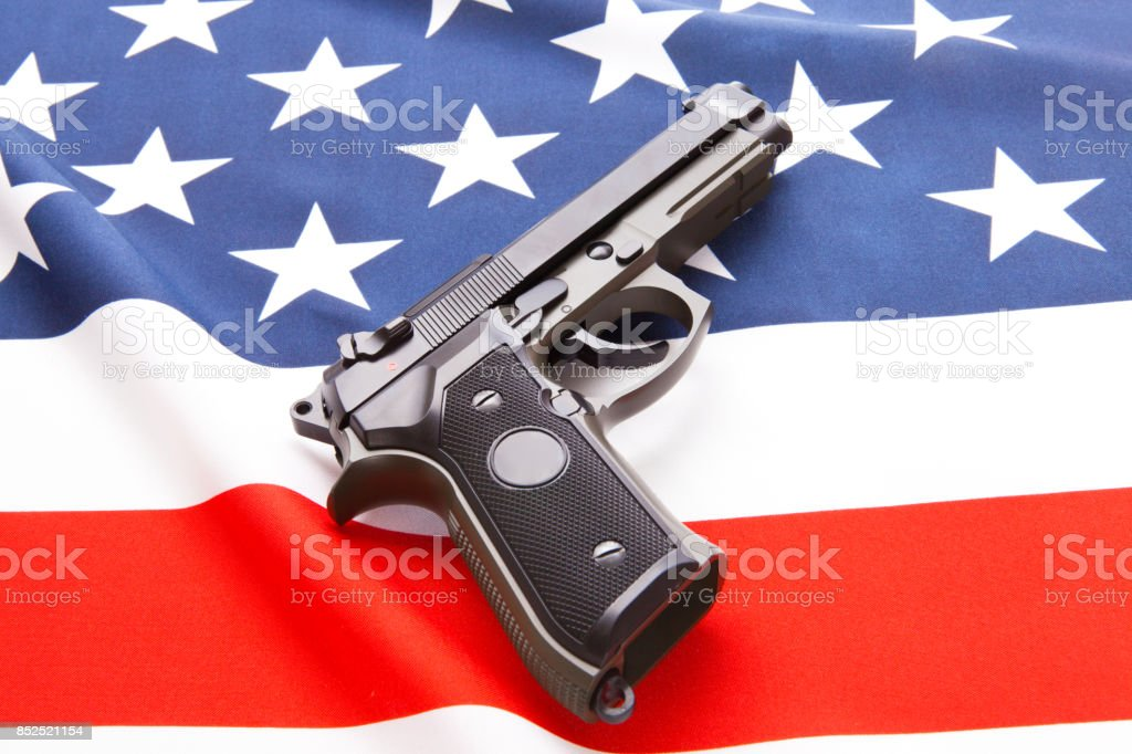 Handgun over satin US flag - studio shoot stock photo