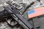 Handgun over USA solder's uniform and shoulder patch on it