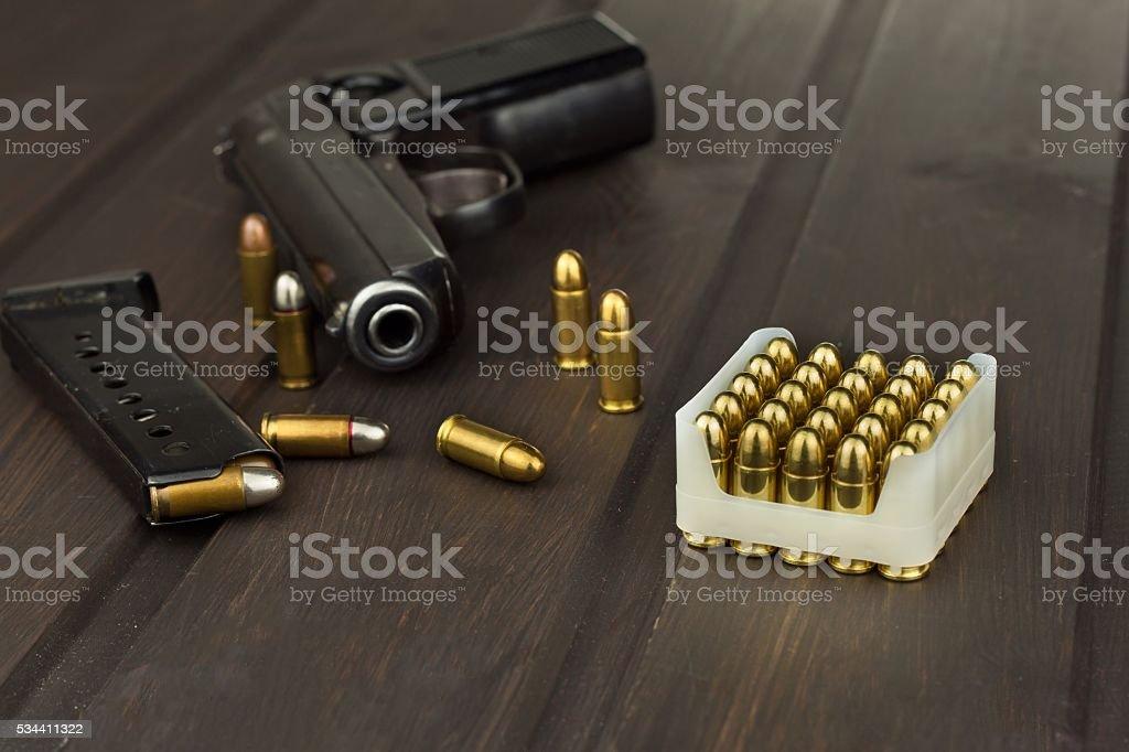 Handgun with ammunition on a dark wooden table stock photo