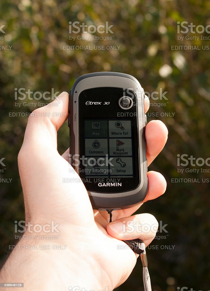 Handheld GPS transmiter Garmin in hand on nature stock photo