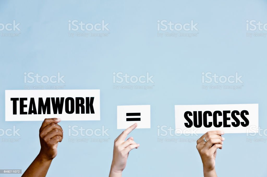 Hand-held signs read 'Teamwork = Success' against sky blue stock photo