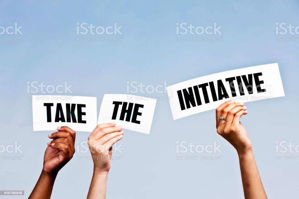 Hand-held signs say ' Take the initiative' against sky blue stock photo