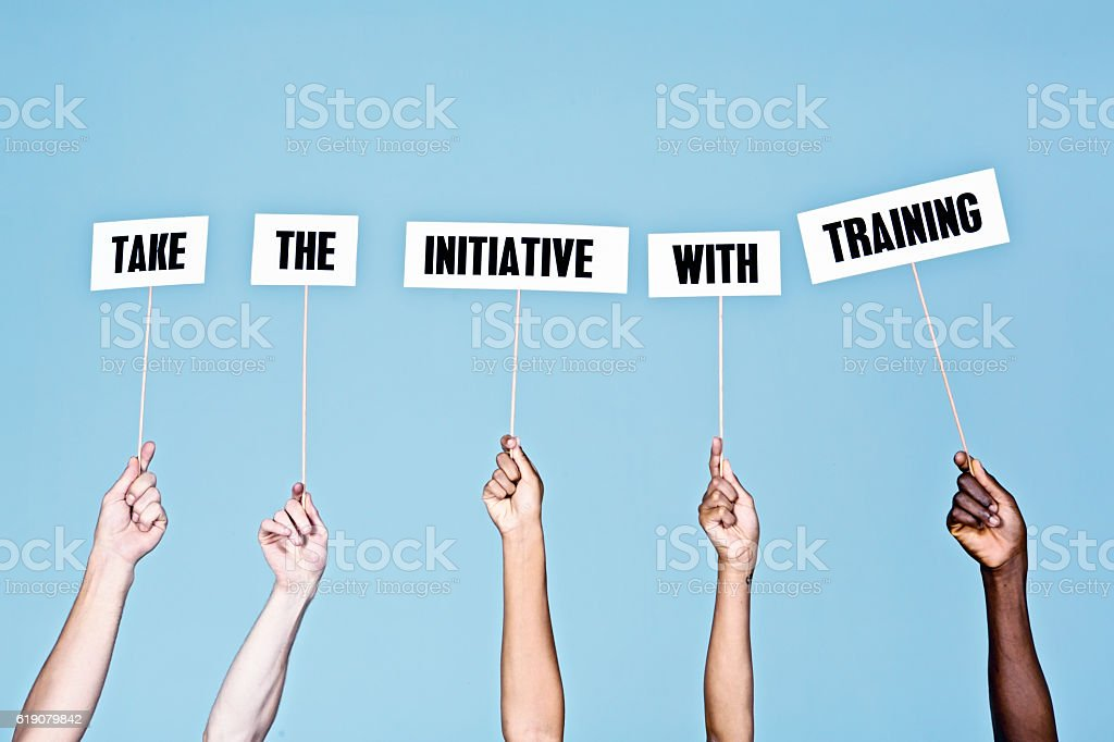 Hand-held signs say 'Take the initiative with training' stock photo