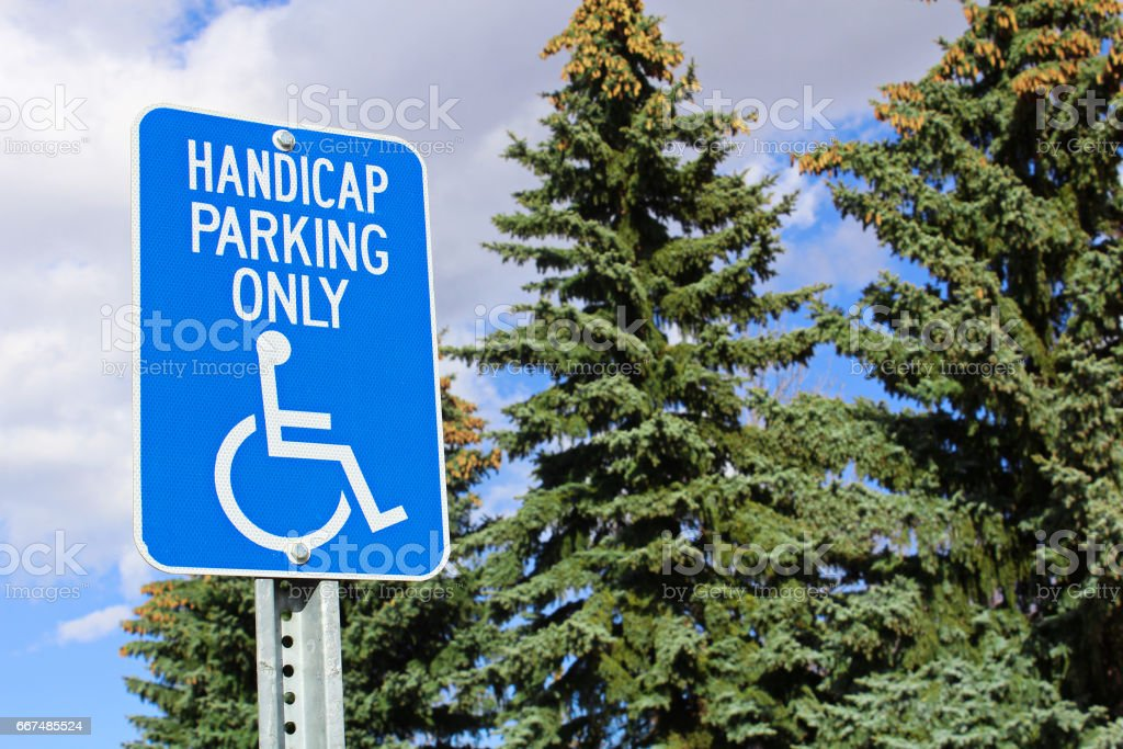 Handicap parking sign with trees in the background stock photo