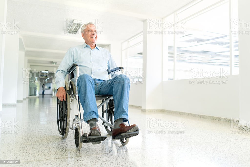 Handicap senior man at the hospital in a wheelchair stock photo