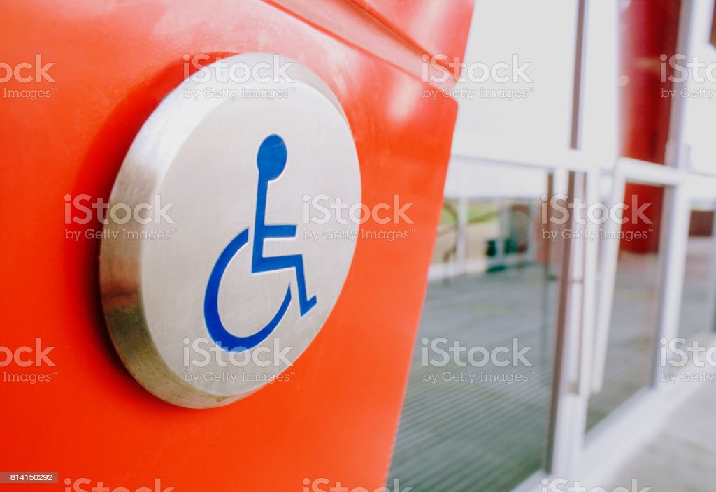 Handicap sign and open door button at entrance of building. stock photo