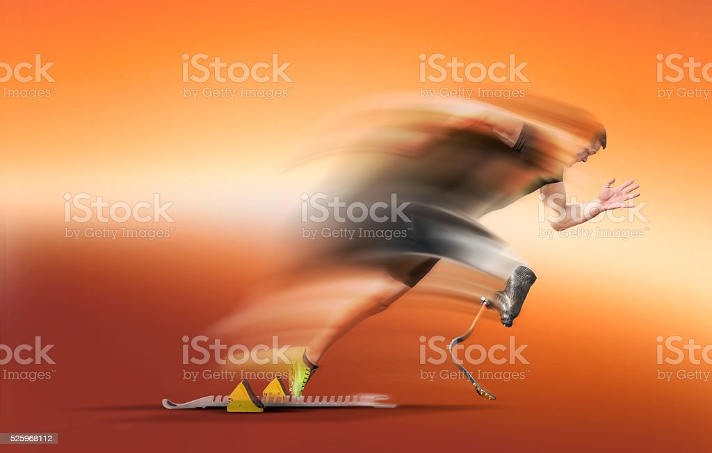 Handicapped athlete motion blurred start out of blocks stock photo