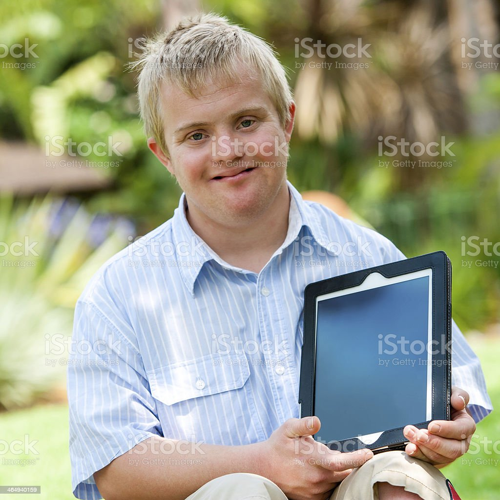 Handicapped boy holding tablet outdoors. stock photo