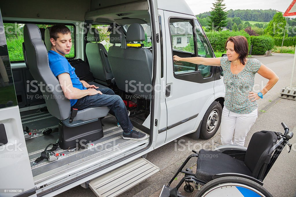 Handicapped boy is picked up by school bus stock photo