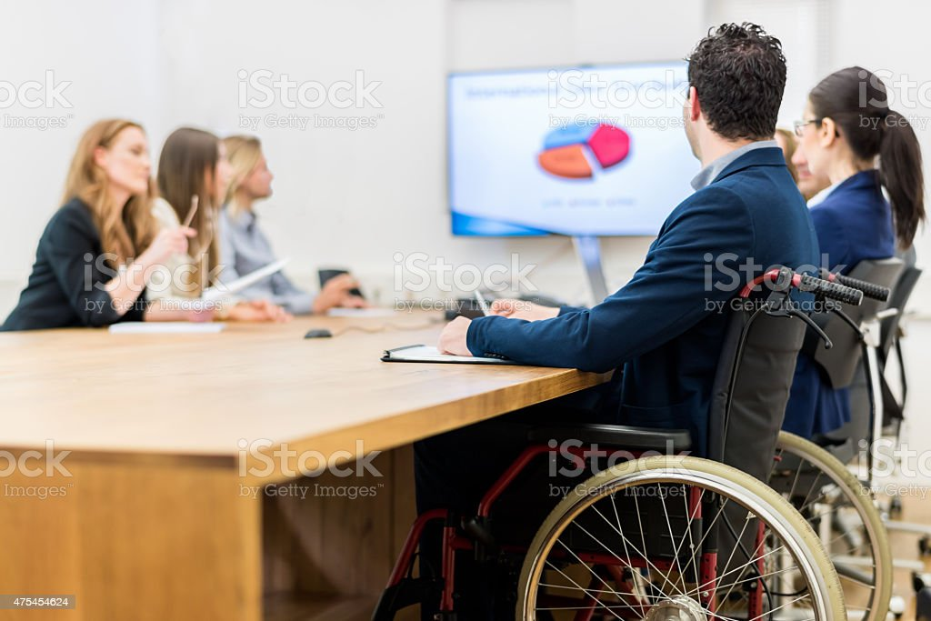 Handicapped Businessman Sitting On Wheelchai in Business Meeting stock photo