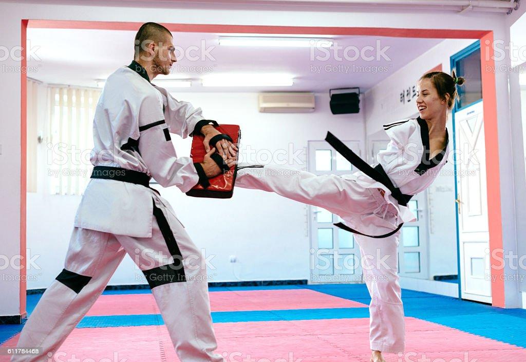Handicapped martial arts trainee kicks punching bag stock photo