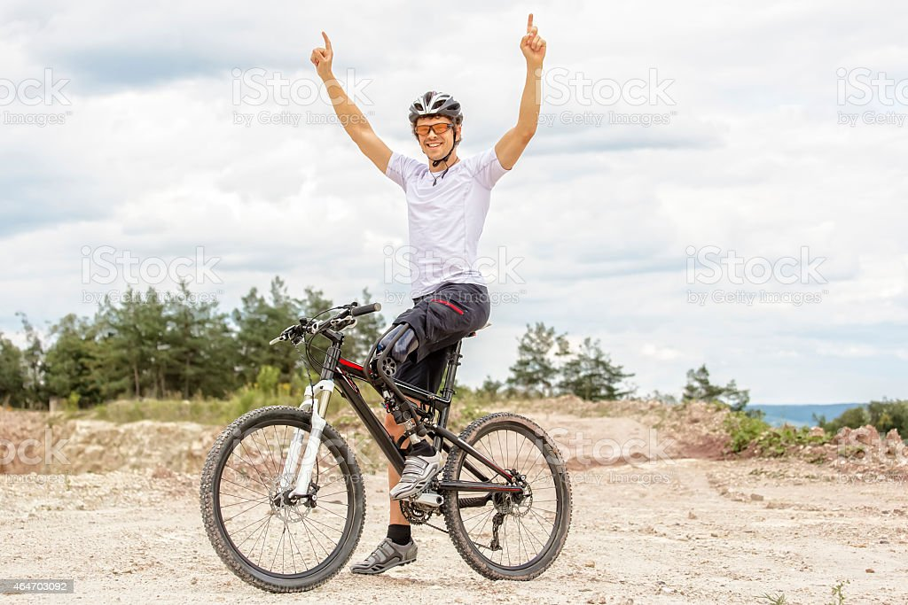 Handicapped mountain bike raising up arms stock photo