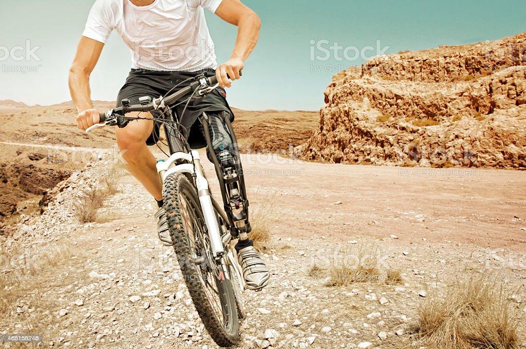 Handicapped mountain bike rider barren landscape stock photo