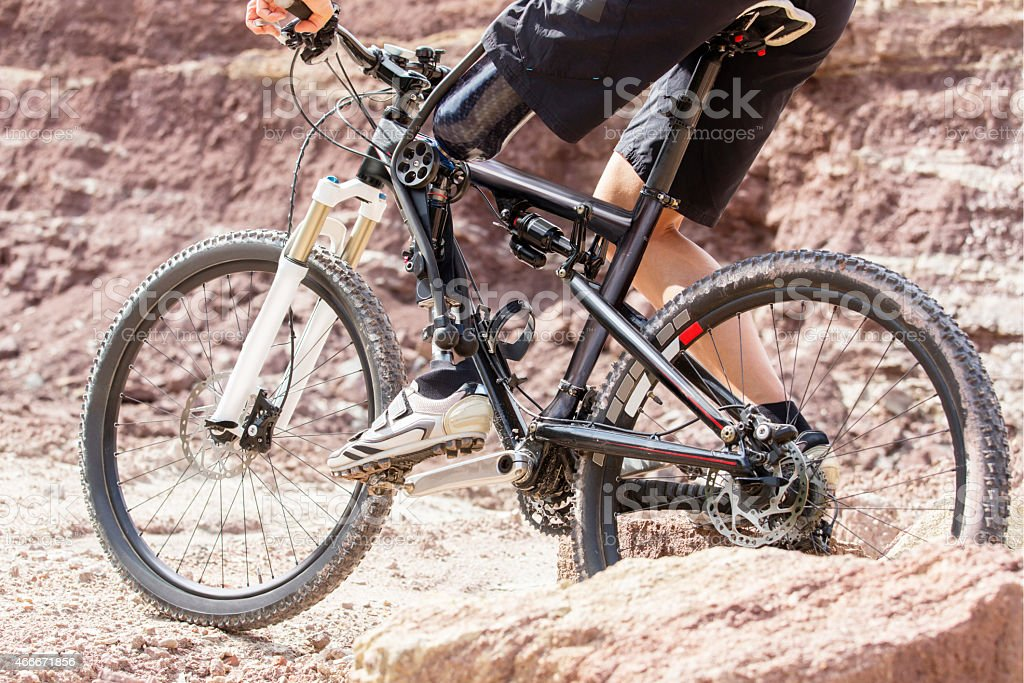Handicapped mountain bike rider between rocks stock photo