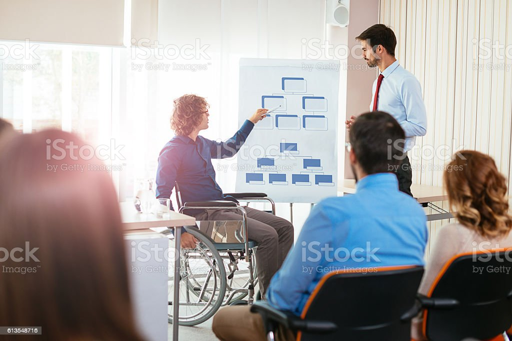Handicapped person on seminar explains corporate hierarchy stock photo
