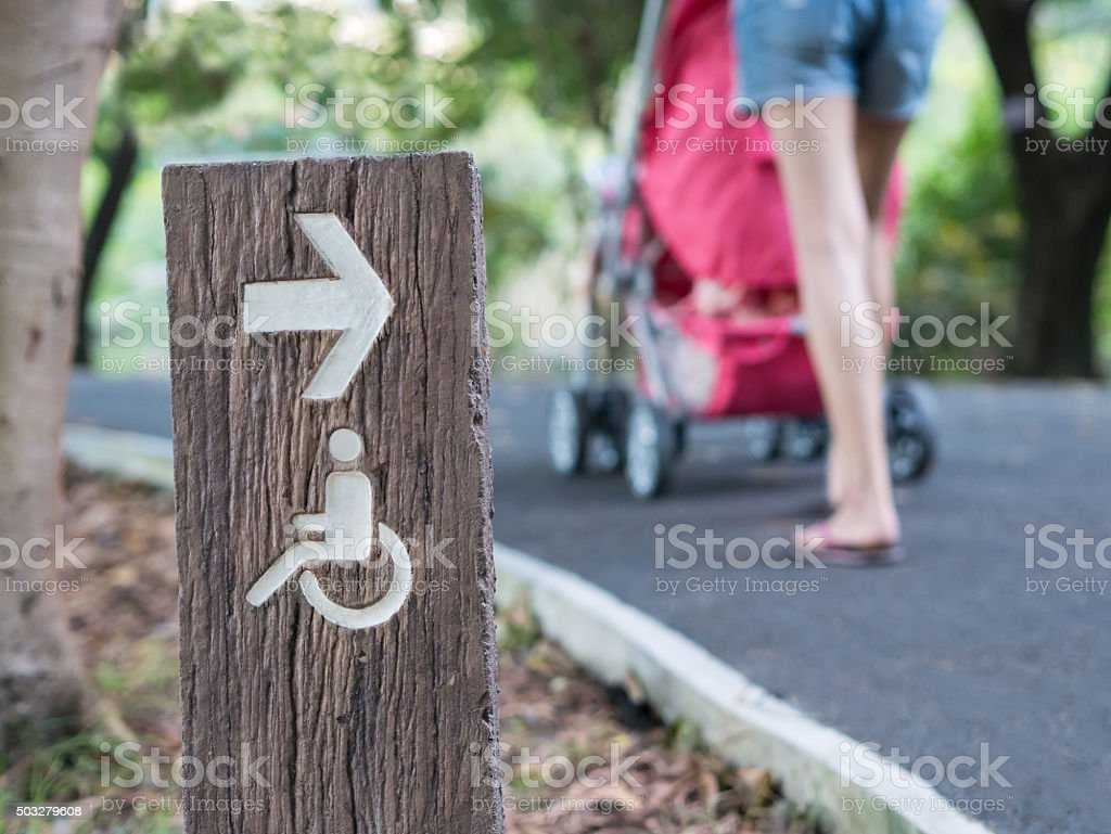Handicapped sign in park with blurry family background. royalty-free stock photo