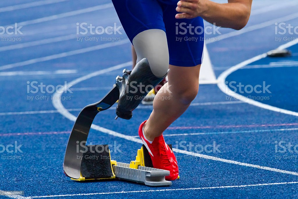 Handicapped sprinter on blue track stock photo