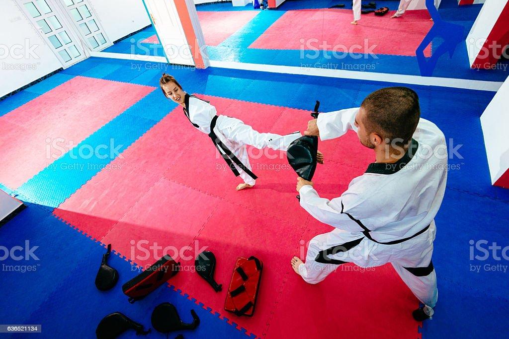 Handicapped taekwondo trainee kicks focus pads stock photo