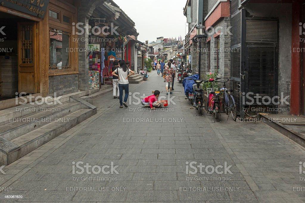 Handicapped vagrant beggar in Beijing Hutong stock photo