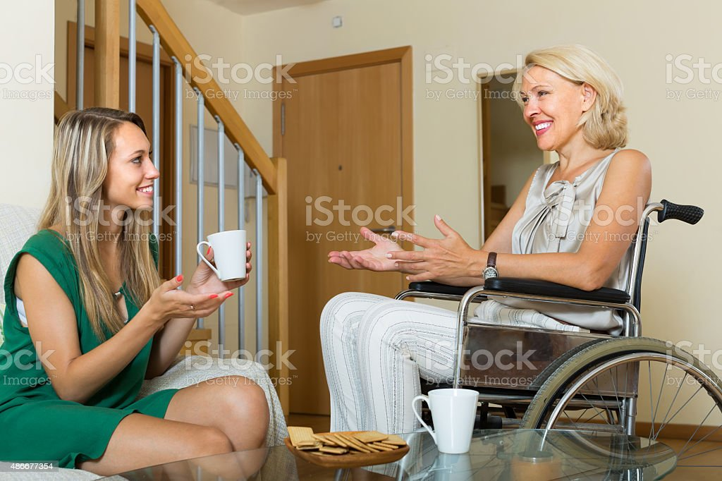 Handicapped woman with guest at the table stock photo